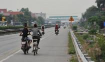 Xe máy vừa đi vừa đẩy xe đạp có bị xử phạt?